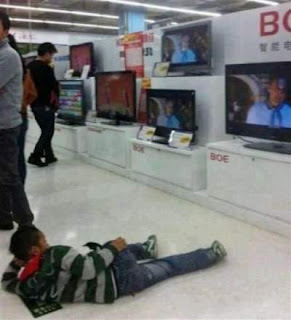 watching television in shopping mall laying on the floor - funny