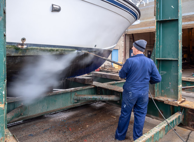 Photo of Phil using the pressure washer on Ravensdale's hull