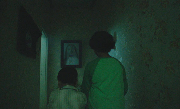 Ian (M. Adhiyat) and Bondi (Nasar Annuz) are both having trouble facing their late mother's photo frame in PENGABDI SETAN (2017)