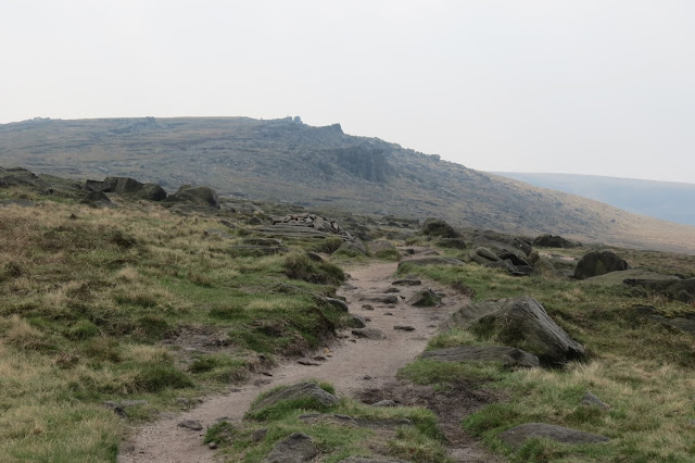 A sandy path though rocks and grass, with the Blackstone Edge escarpment in the background.