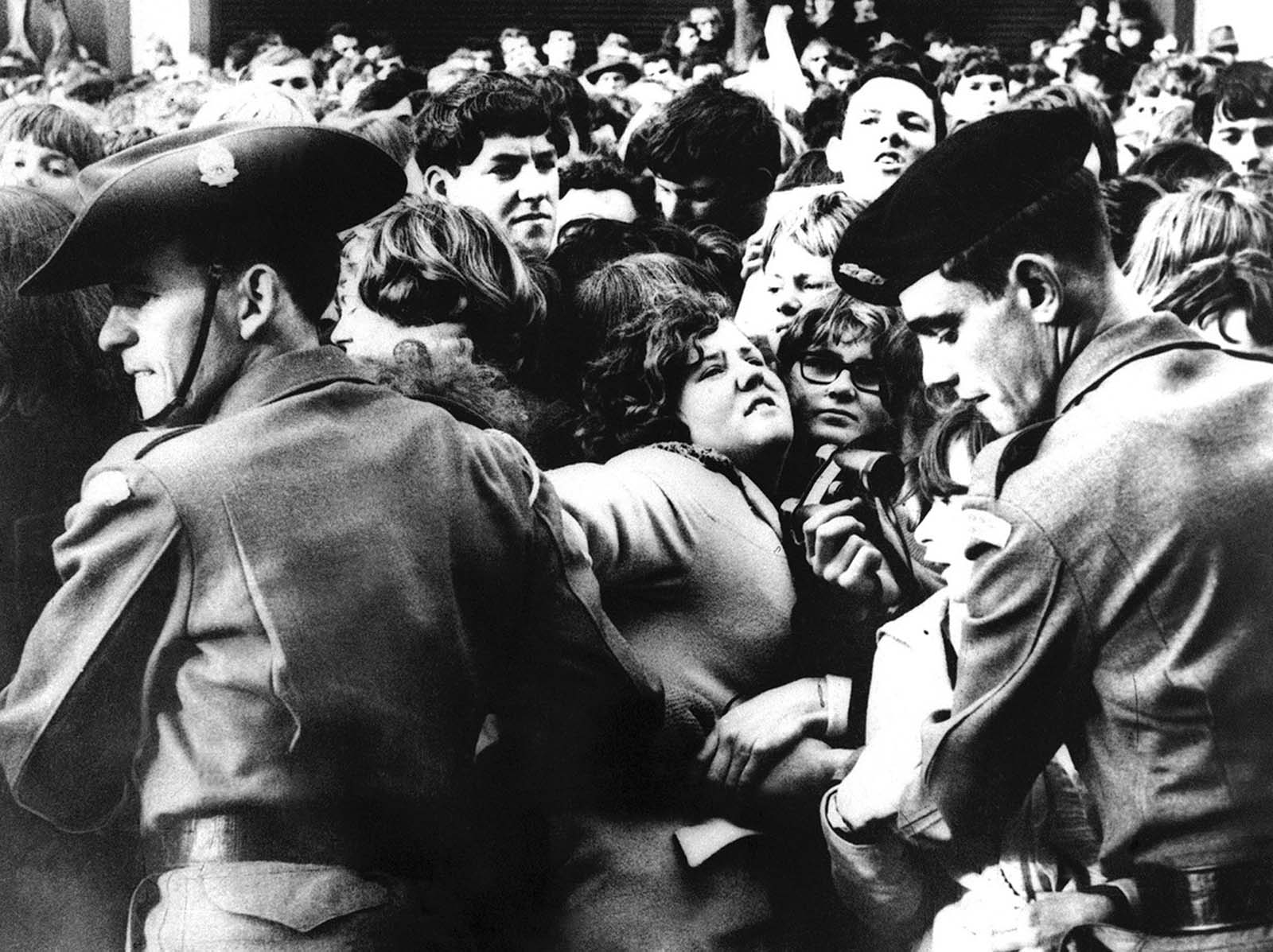 Two Australian soldiers link arms to control a section of the crowd outside the Southern Cross Hotel in Melbourne on the arrival of the Beatles, on June 14, 1964. Some 300 policemen and 100 soldiers made an attempt to contain 10,000 screaming fans and to keep open a passageway for the singing group's cars. Like most of the barriers, this one was pushed aside at the height of the crush. The Beatles were eventually taken into the hotel through a back entrance.
