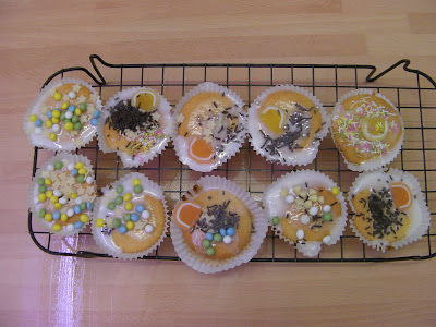homemade fairy cakes with decorations on wire drying rack
