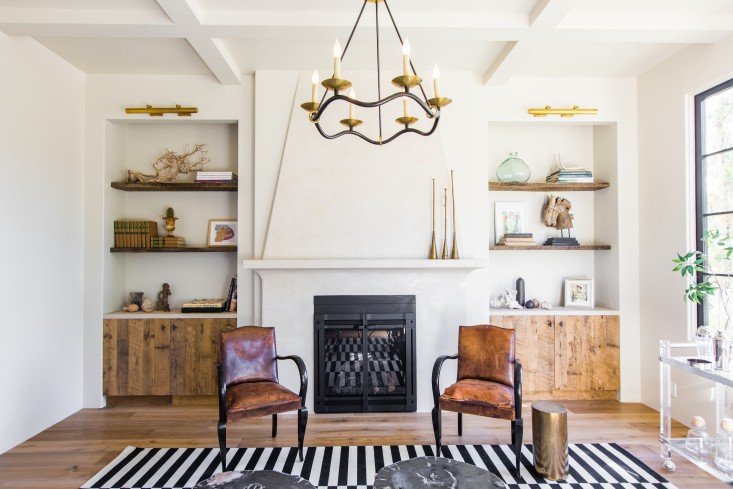 """The same wood cabinetry from the kitchen puts in an appearance in the living room, which is anchored by a Spanish-style fireplace, Ikea rug, and midcentury-inspired light, the Choros Chandelier from Circa Lighting. All the pale surfaces, including the coffered ceiling, are Venetian plaster. """"It's actually a beige that reads as white."""" The lucite bar cart came from eBay. COME SEE MORE Rustic Spanish Villa Interior Design Inspiration!"""