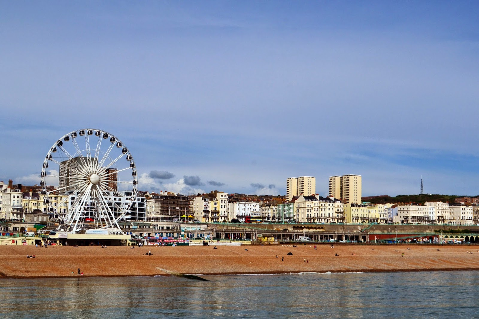 a view of brighton from the end of the pier. A big wheel, shops, and hotels can be seen on the shore