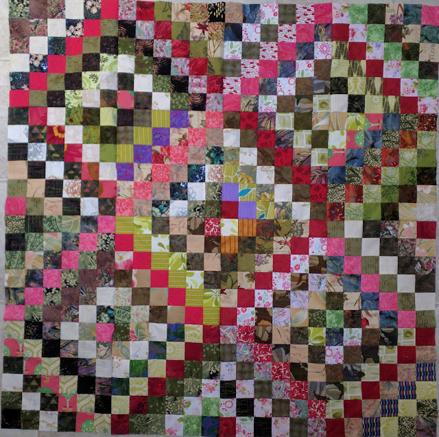 Green Scrappy Trip quilt with pinks and reds on the main diagonal