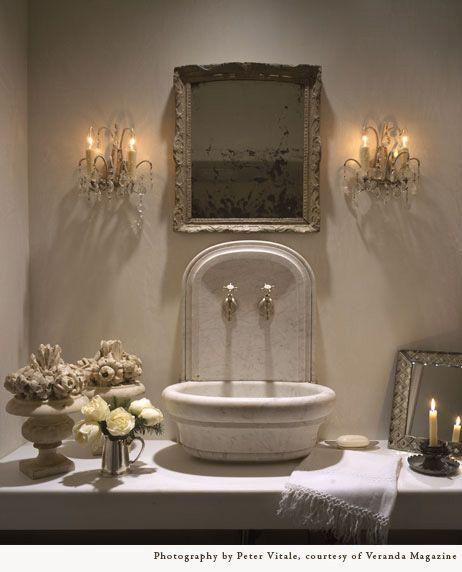 Pamela Pierce designed bathroom with antique stone sink and crystal sconces. #luxuriousbathroom #frenchcountry #oldworldstyle #interiordesign