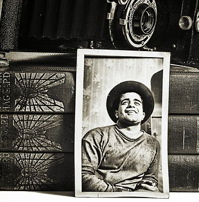 A young man in his 20s, circa 1930s; a photo leaning against a stack of old books.