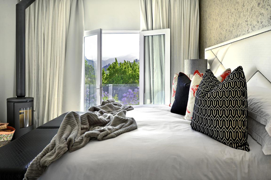 bed, white linen, fire place, bedroom, accommodation, betty bake, holiday, cape town, luxury, modern,