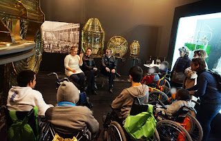 Dentro do Farol Museu, na casa das lâmpadas, alunos, equipa técnica do Museu, os dois faroleiros, professora e restantes acompanhantes conversam
