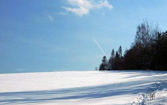 Samolot rysuje na błękicie białą kreskę smugi kondensacyjnej.