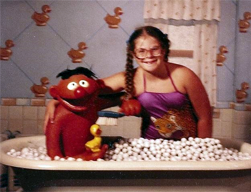 image of me at 10 years old, with braided pigtails and oversized glasses, wearing a purple one-piece bathing suit featuring a cheetah across the midsection, posing in a 'bubble bath' next to Ernie at Sesame Place