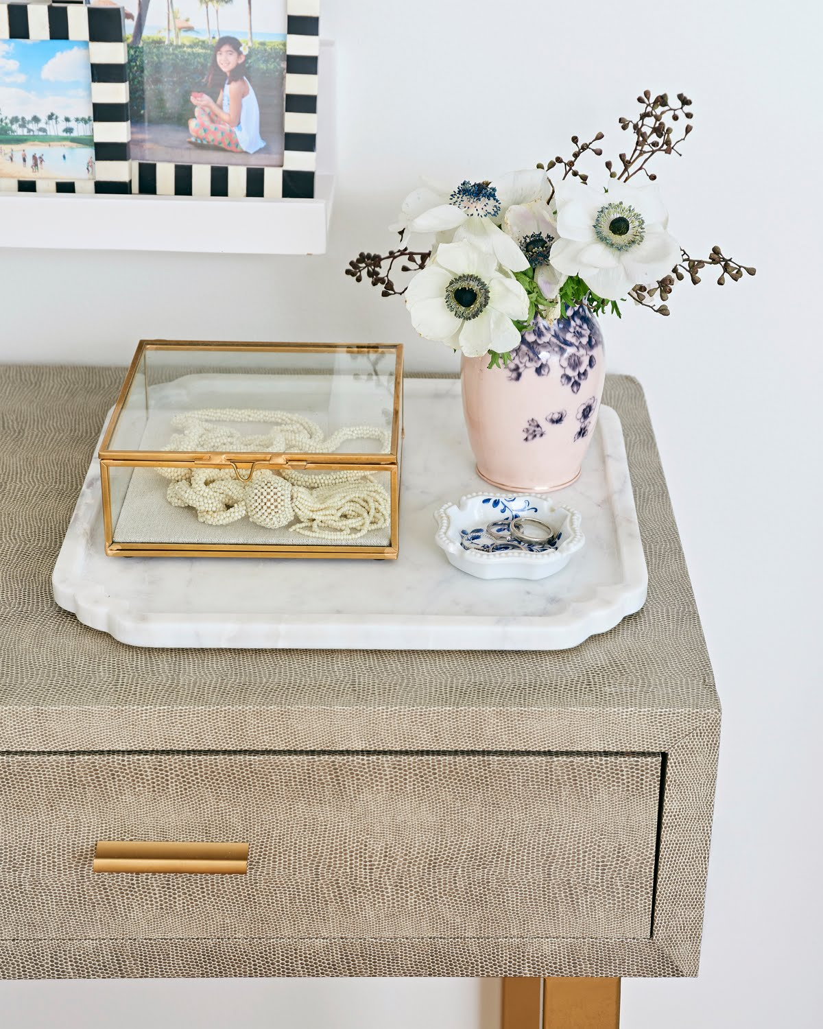 black and white frames with family photographs, a vase with anemones, gold glass box on marble tray