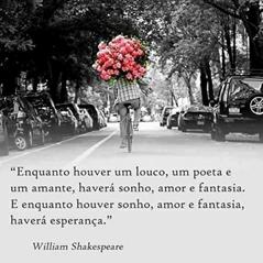 """Foto quadrada em preto e branco. Em uma alameda com as copas das árvores em arco, carros estacionados em ambos os lados, ao centro, de costas, um ciclista de camisa xadrez, calça jeans e tênis, apoia nos ombros um enorme bouquet de flores rosas. Abaixo, lê-se: """"Enquanto houver um louco, um poeta e um amante, haverá um sonho, amor e fantasia. E enquanto houver sonho, amor e fantasia, haverá esperança.""""William Shakespeare."""