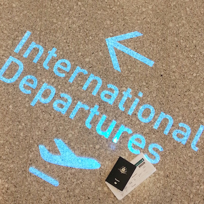 Floor sIgn for international departures, with a passport and boarding pass next to it.
