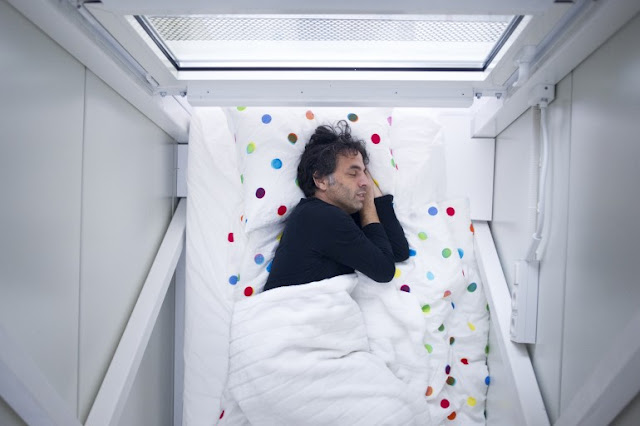 Picture of Keret sleeping in his bed in the bedroom of world's narrowest house