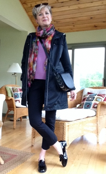 woman in black raincoat, black pants, pink sweater and oversize sunglasses