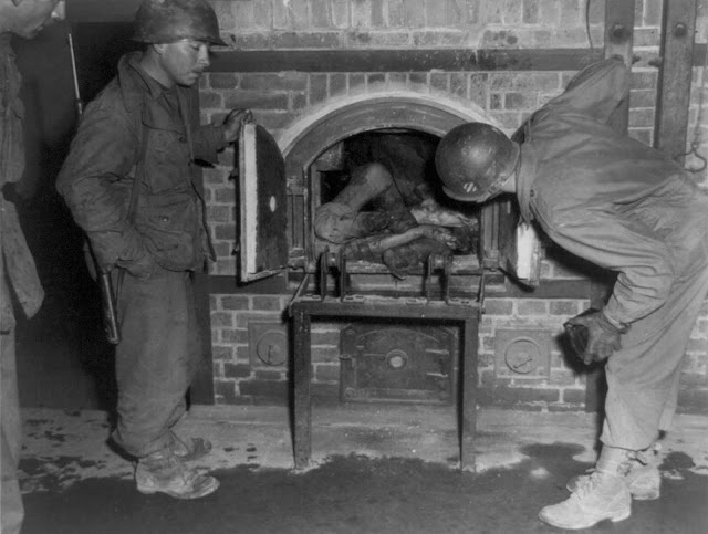 Three U.S. soldiers look at bodies stuffed into an oven in a crematorium in April of 1945. Photo taken in an unidentified concentration camp in Germany, at time of liberation by U.S. Army.