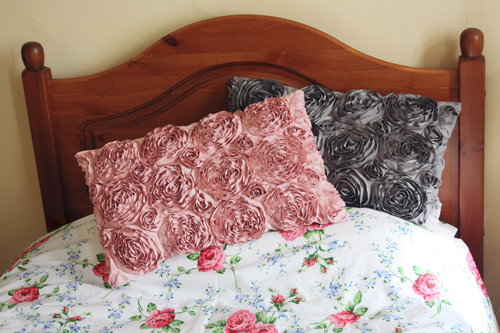 two cushions, both the same design, with three dimensional flowers embellished. One cushion is grey, one is pink. They rest on a bed with a floral duvet