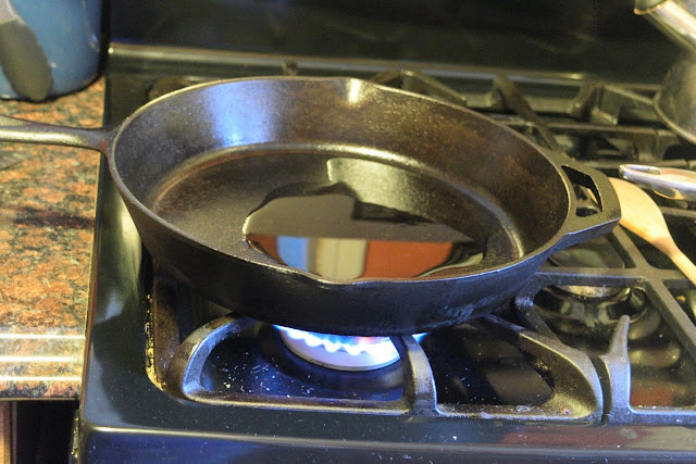 A cast iron skillet over high heat on the stove.