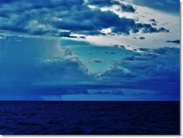 Waterspouts drop from dark clouds on a dark and stormy ocean horizon.