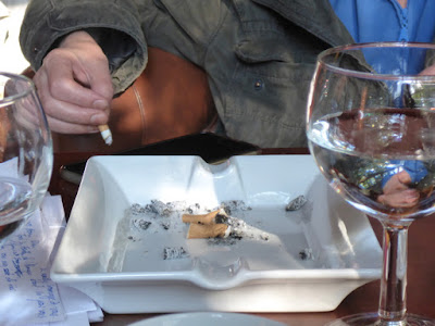 Zigarettenhand, Ascher, Gesicht spiegelt sich im Wasserglas
