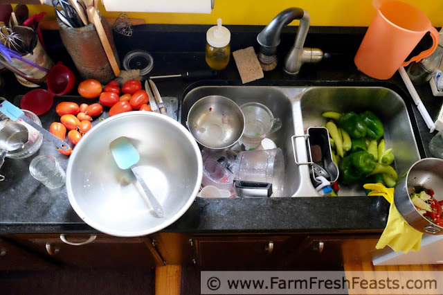 a busy kitchen counter with tomatoes and peppers waiting to be prepped