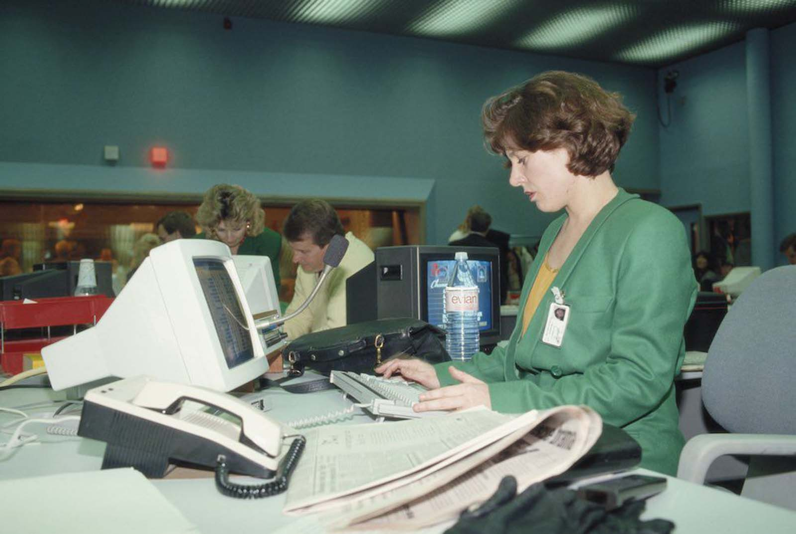 An office worker during the launch of Sky TV in London. She wears a green double-breasted jacket, possibly part of a uniform. Her hair is feathered in layers. In the background another woman wears a similar jacket. Her hair is bleached and waved over large earrings. 1989.