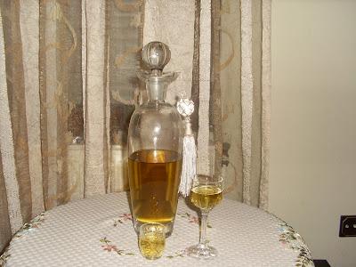 Ωραία καράφα με λικέρ αρωματικό απο δυόσμο και δυο πανέμορφα ποτηράκια γεμάτα με λικέρ,πάνω σε ένα τραπέζι,φόντο πισω όμορφη κουρτίνα