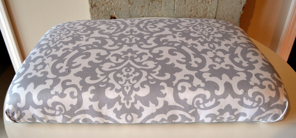 Gray and white fabric upholstered cushion