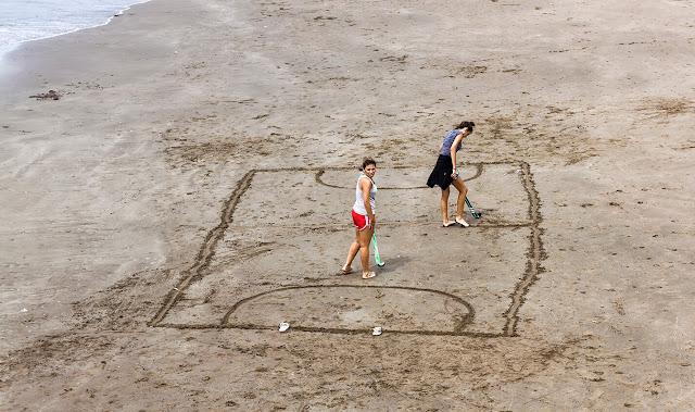 Dos mujeres en la arena marcando una cancha para jugar hockey