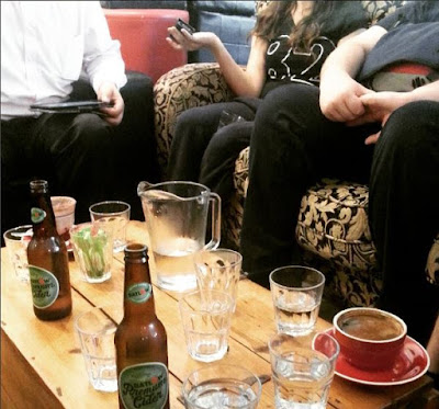 Group of people sitting around a coffee table filled with various drinks and glasses.