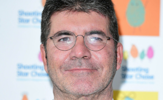 Simon Cowell stretchered out of his house and rushed to hospital by ambulance after falling down the stairs at his London home