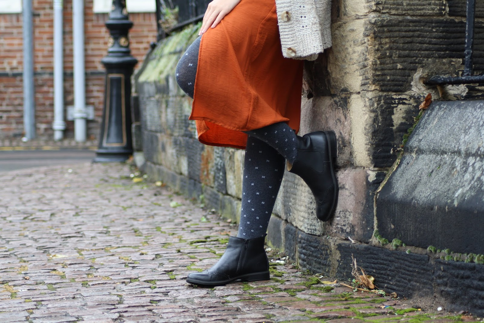 Abbey, resting one leg against the wall, wears knit tights, orange dress, and black leather boots