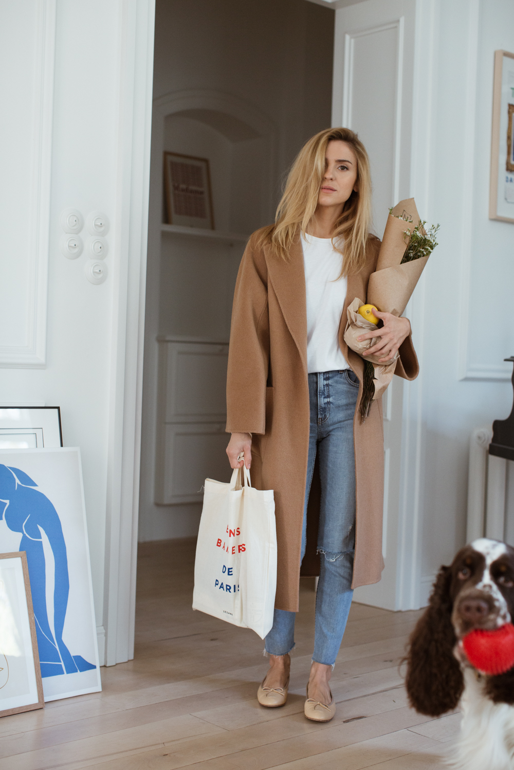 Fall and Winter Weekend Outfit Idea for Running Errands — Katarzyna Tusk in aCamel Coat, Raw-Hem Jeans, and Beige Ballet Flats