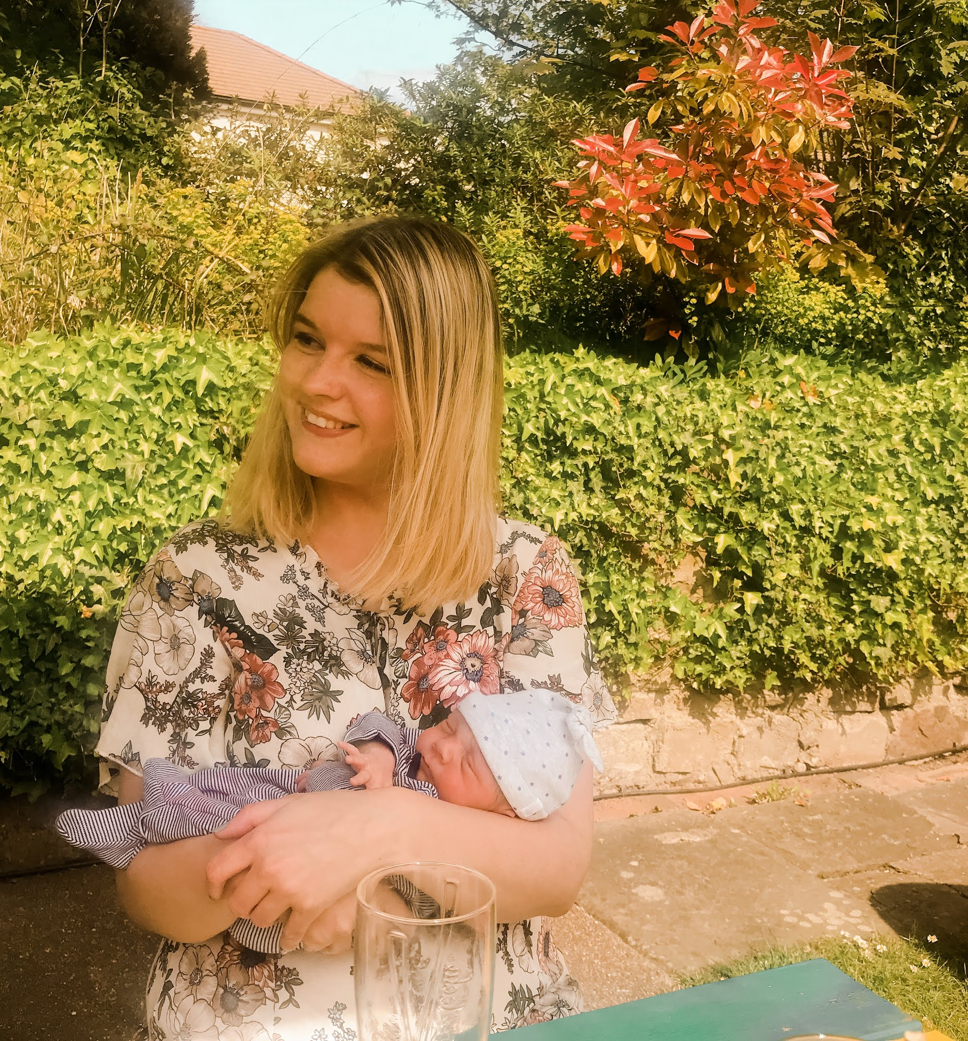 Fashion blogger Chloe Harriets smiling and holding baby relative
