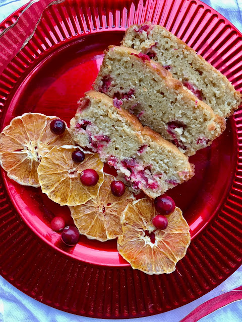 Slices of cranberry orange bread on a plate with dried orange slices and fresh cranberries.