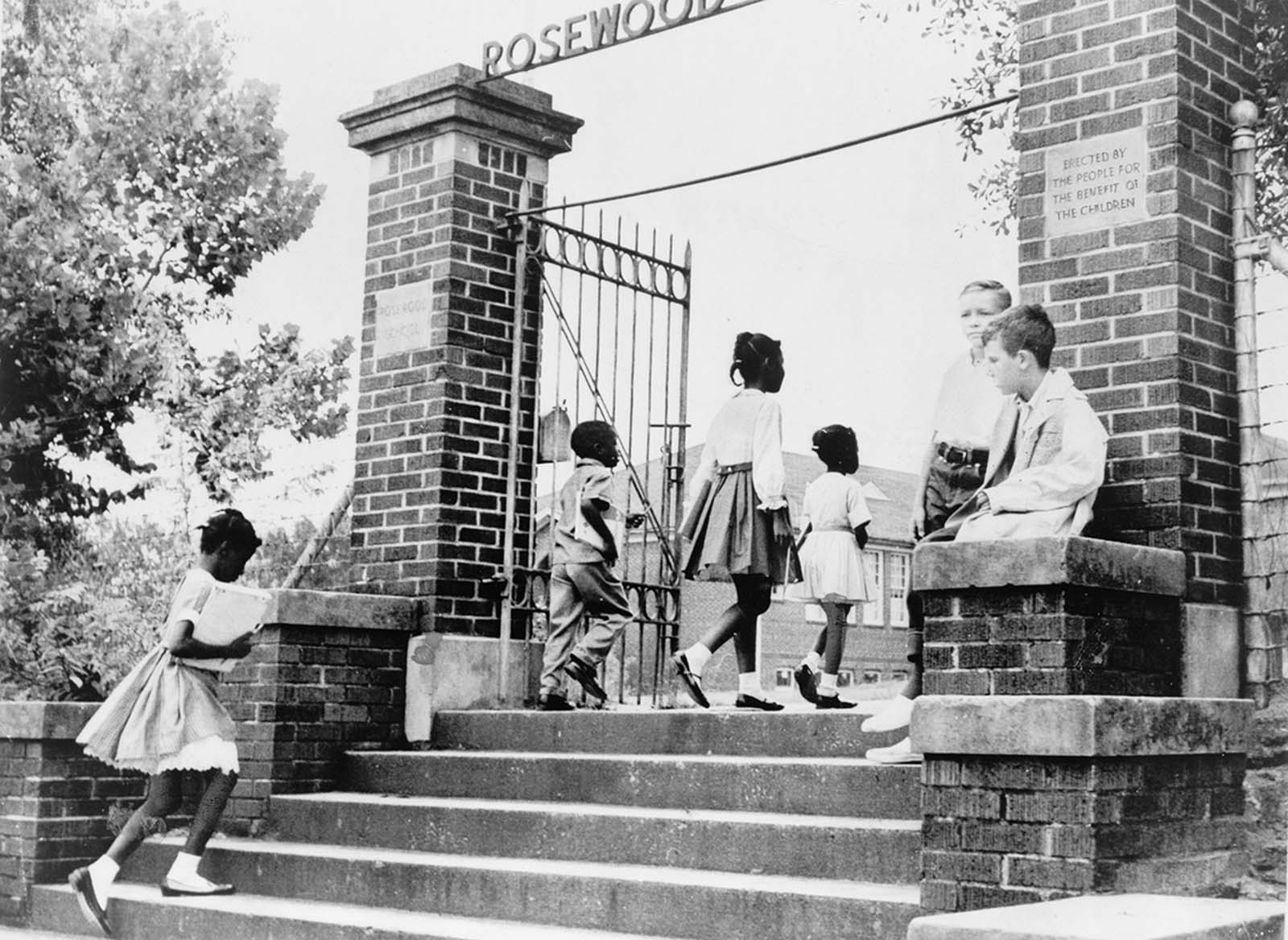 Two white students watch as African American children enter the previously all-white Rosewood Elementary School in Columbia, South Carolina, on August 31, 1964.