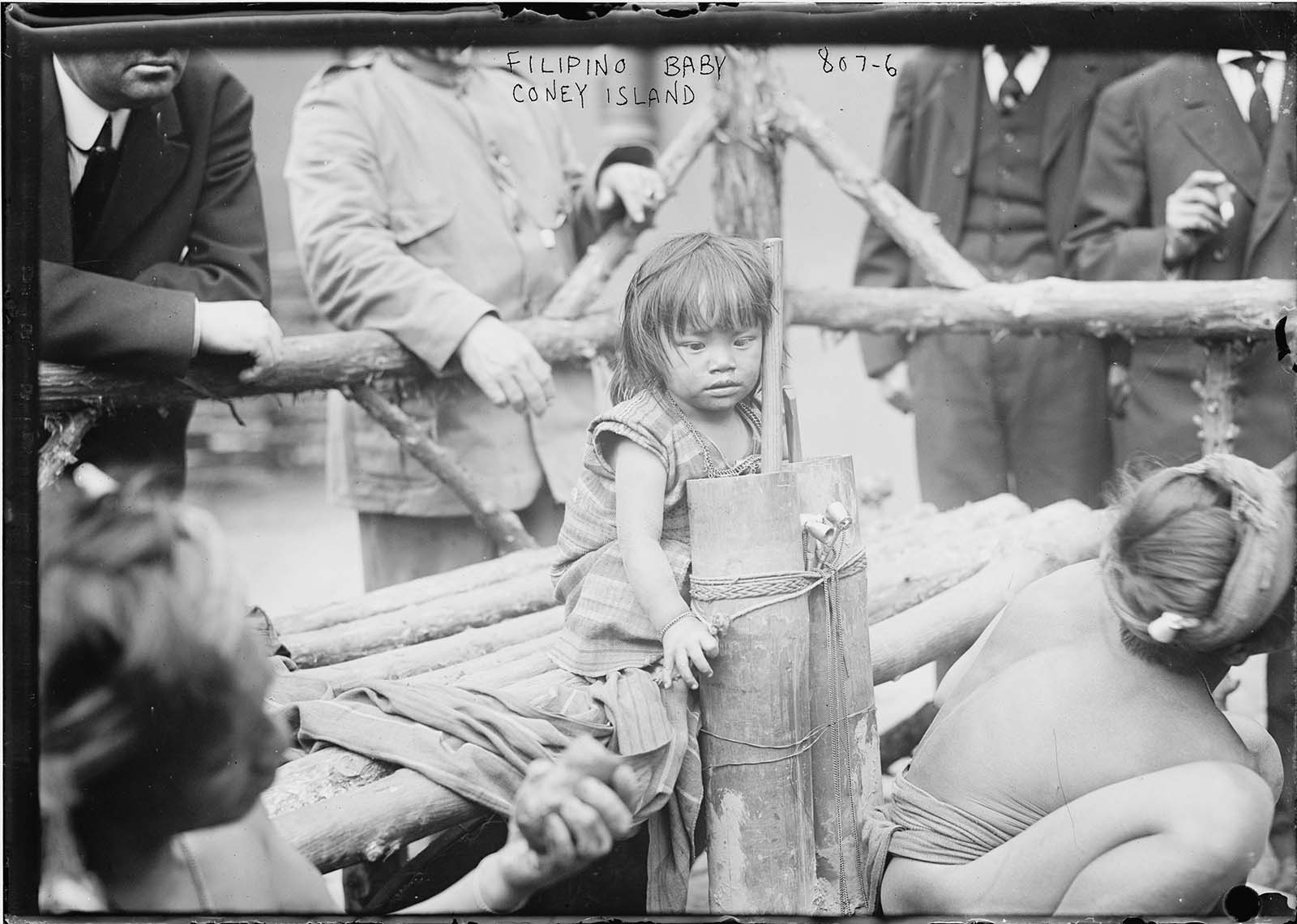 A young Filipino girl is pictured sitting on a wooden bench in an enclosure in Coney Island, New York in another horrifying 1906 'exhibit'.