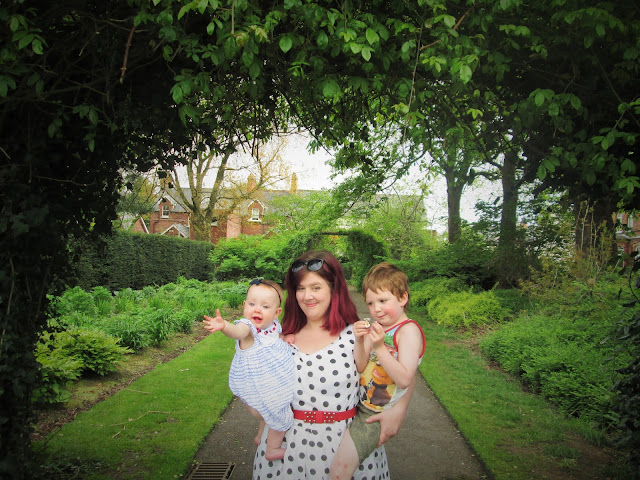 Up close photo of us under green leafy arches with D showing off his daisy and Baby S holding her hand out to Daddy (our Mummy and Me Photo for May)