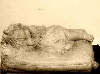 Escultura em pedra de anjo deitado sobre uma almofada, vista no Museu Municipal de Caxias do Sul.