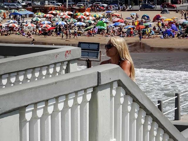 Joven en escalera y de fondo la gente en la playa.