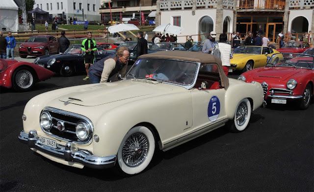 Beiger Nash- Healy Roadster Pininfarina auf der Passione Engadina, Viele Autos auf Parkplatz vor Kulm Country Hotel