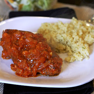 greek cinnamon stewed chicken on a white plate with rice