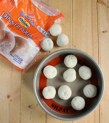 rhodes frozen rolls arranged on silpat in pan to defrost