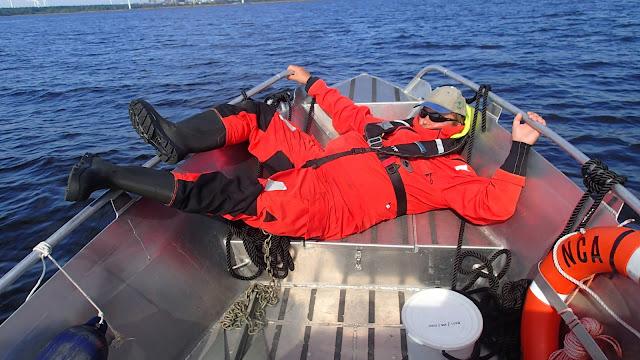 Pelastautumispukuinen henkilö retkottaa veneen keulassa