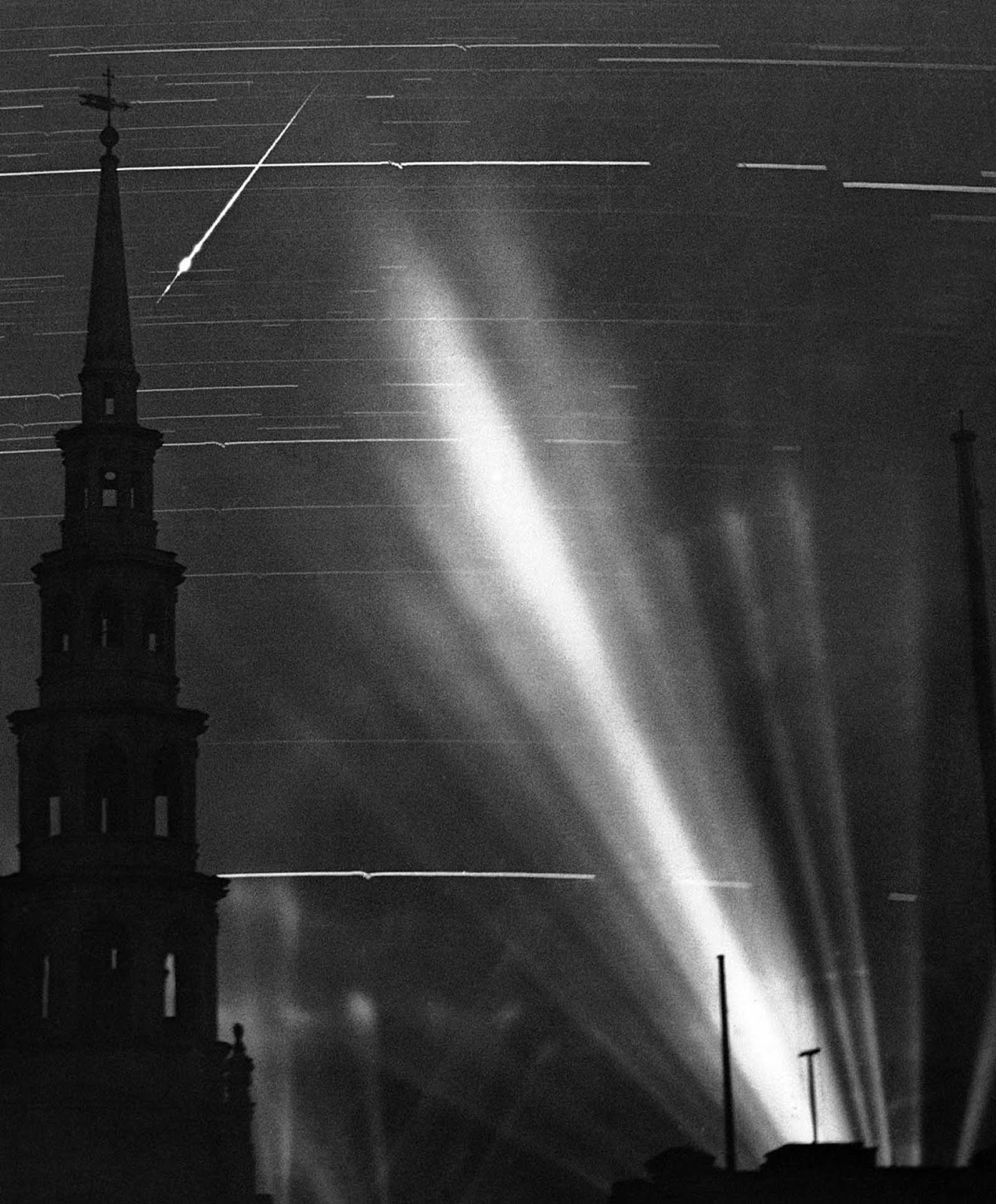 A ninety minute exposure taken from a Fleet Street rooftop during an air raid in London, on September 2, 1940. The searchlight beams on the right had picked up an enemy raider. The horizontal marks across the image are from stars and the small wiggles in them were caused by the concussions of anti-aircraft fire vibrating the camera. The German pilot released a flare, which left a streak across the top left, behind the steeple of St. Bride's Church.