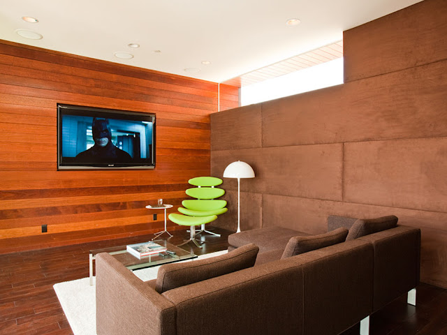 Picture of the movie room with wooden wall and dark brown sofa