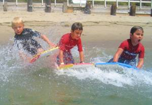 Three boys boogie boarding side by side at summer camp.