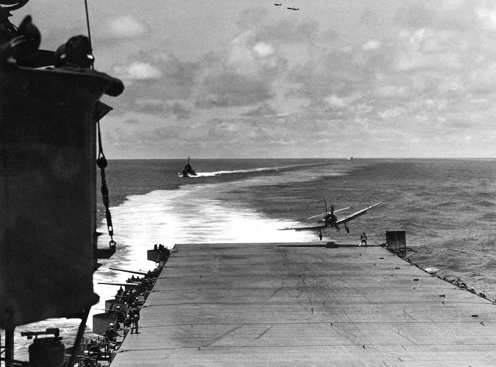 A VB-8 SBD lands far off center, flying right over the head of the Landing Signal Officer aboard USS Hornet during the Battle of Midway, on June 4, 1942.