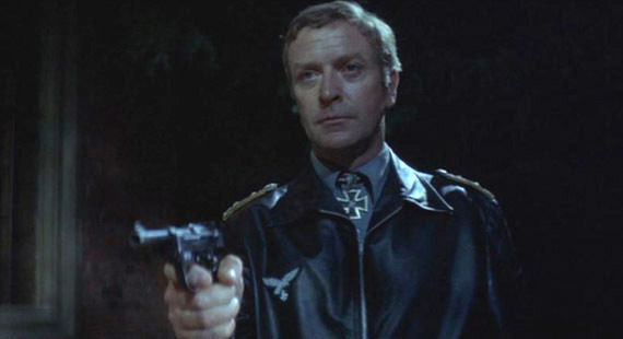 Michael Caine in German uniform pointing a Luger pistol